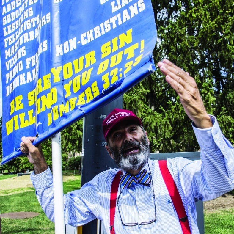 """Brother Jed Smock from Campus Ministry USA in Terre Haute holds a sign listing the kinds of people they say are damned to Hell in a crowd of protestors at the Scramble Light on Sept. 23. Campus Ministry, according to their website, use """"confrontational Evangelism"""" to rebuke those they believe to be sinners. Samantha Brammer, DN File"""