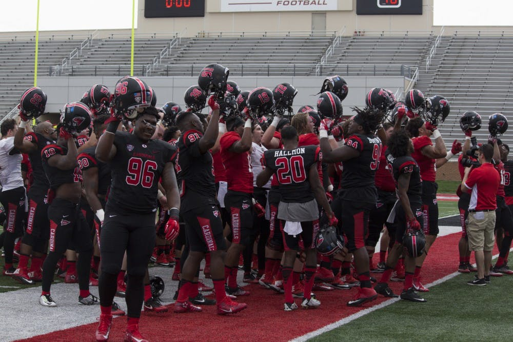 The Ball State football team raises their helmets and sings the school's fight song after their spring game at Scheumann Stadium on April 15. The game marked the end of the team's spring practices. Briana Hale // DN