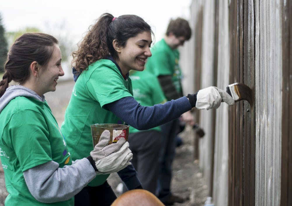 Volunteers help at Munice Missions on April 22. They were a part of a volunteer documentary called Shoot for Good. Chelsea Scofield // DN File