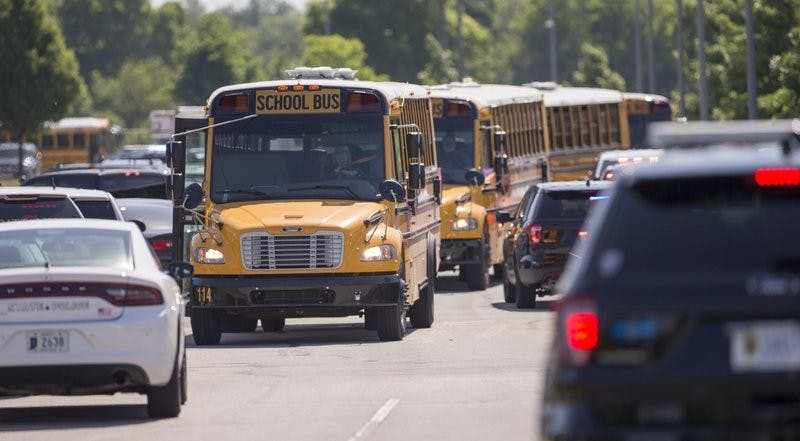 Empty school buses leave after a shooting at Noblesville West Middle School in Noblesville, Ind., on Friday, May 25, 2018. A male student opened fire at the suburban Indianapolis school wounding another student and a teacher before being taken into custody, authorities said. AP Photo
