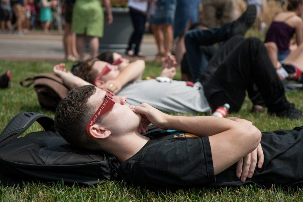 Students and community members gather on the University Green on Aug. 21 for the Eclipse Viewing Party. 93 percent of the sun was covered by the moon by 2:25pm. Kaiti Sullivan // DN
