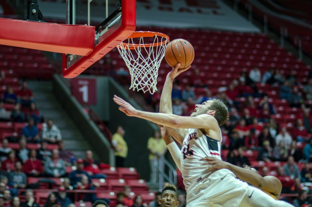 Sophomore forward Kyle Mallers jumps up for a layup while being grabbed by a Kent State opponent Feb. 9 at John E. Worthen Arena. Ball State won the game 87-68. Stephanie Amador, DN