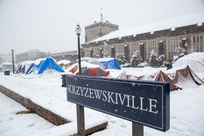 Students build snowmen and salvage their tents weighed down with snow in Krzyzewskivlle.