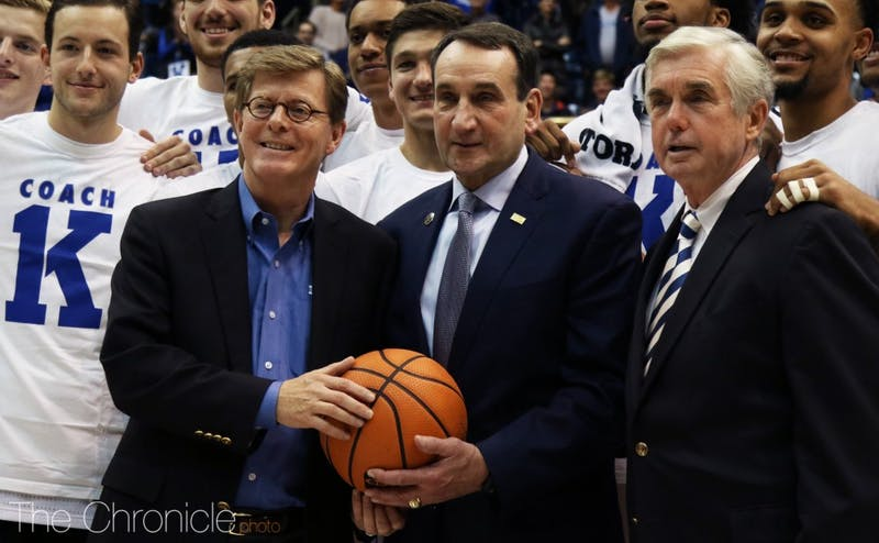 Coach Mike Krzyzewski celebrated his 1,000th win at Duke alongside his team, receiving a game ball from President Vincent Price and Director of Athletics Kevin White.