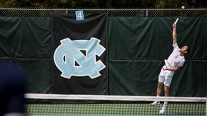 Senior Robert Kelly serves against Virginia on April 1 at the Cone-Kenfield Tennis Center.