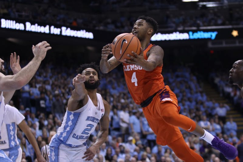 Clemson's Shelton Mitchell (4) takes a layup on Jan. 16 in the Smith Center as Joel Berry II (2) and Luke Maye (32) defend.