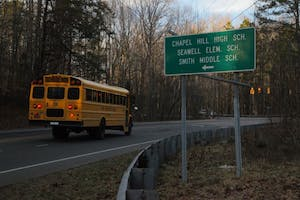 A Chapel Hill-Carrboro City Schools bus drives towards Chapel Hill High School.