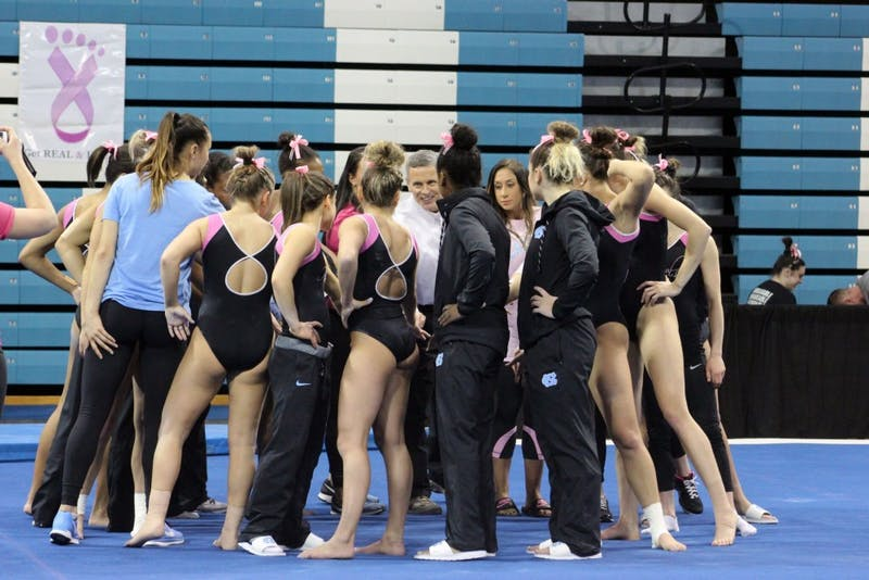 The North Carolina gymnastics team huddles before its Pink Meet against Brown on Feb. 19 in Carmichael Arena.