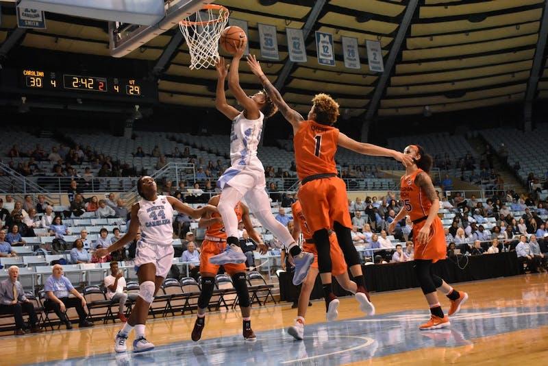 UNC guard Paris Kea (22) gets past Virginia Tech's defenders to take her shot.