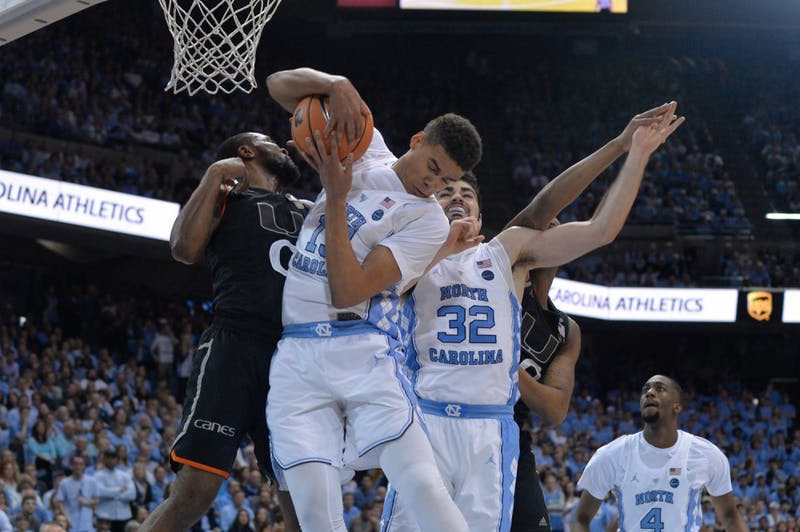 North Carolina guard Cam Johnson (13) goes for a rebound against Miami defenders on Feb. 27 at the Smith Center.