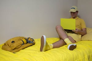 "Benjamin Davis, campus ""yellow dude"" logs onto his computer among his yellow belongings in his residence hall on Sunday."
