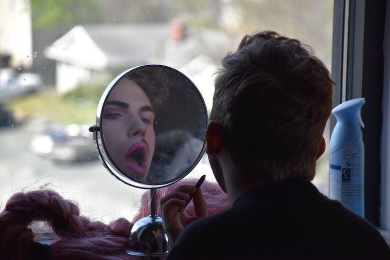 Caleb Puchalski, a.k.a. Doris Locht, puts on makeup. Photo by Summer Lawrence.