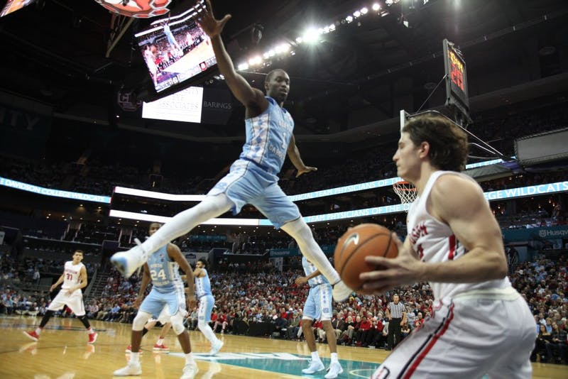 Forward Theo Pinson (1) defends an inbounds pass against Davidson on Dec. 1 in the Spectrum Center in Charlotte.