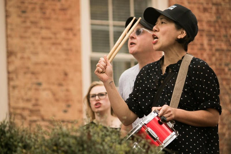 Hong-An Truong, an associate professor of art, accompanied chanting rallyers with a drum beat during Wednesday's anti-fascist rally on UNC campus.