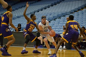 Junior guard Andrew Gillespie (11) drives to the basket in JV men's basketball's win over Word of God in the Smith Center on Feb. 12.