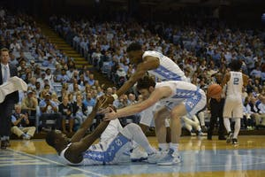 Guard Andrew Platek (3) and forward Brandon Huffman (42) help up teammate Theo Pinson (1) against Bucknell on Nov. 15 in the Smith Center.