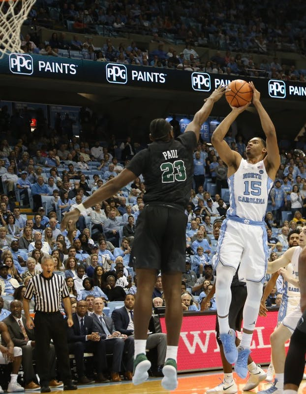 Forward Garrison Brooks (15) shoots over Tulane forward Blake Paul (23) on Dec. 3 in the Smith Center.