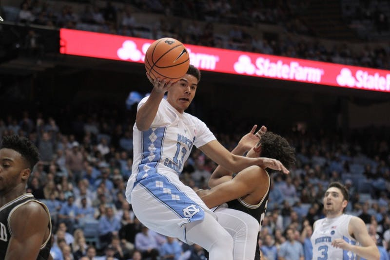 Guard Cameron Johnson (13) falls while taking a layup against Wofford on Dec. 20 in the Smith Center.