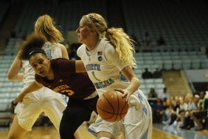 Guard Taylor Koenen (1) dribbles past her opponent on the way to the basket against Minnesota on Nov. 29.