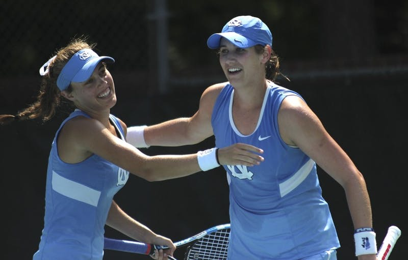 Hayley Carter (right) celebrates with her teammate Maggie Kane after breaking the ACC record for most singles wins during an April 22 match against Pittsburgh.