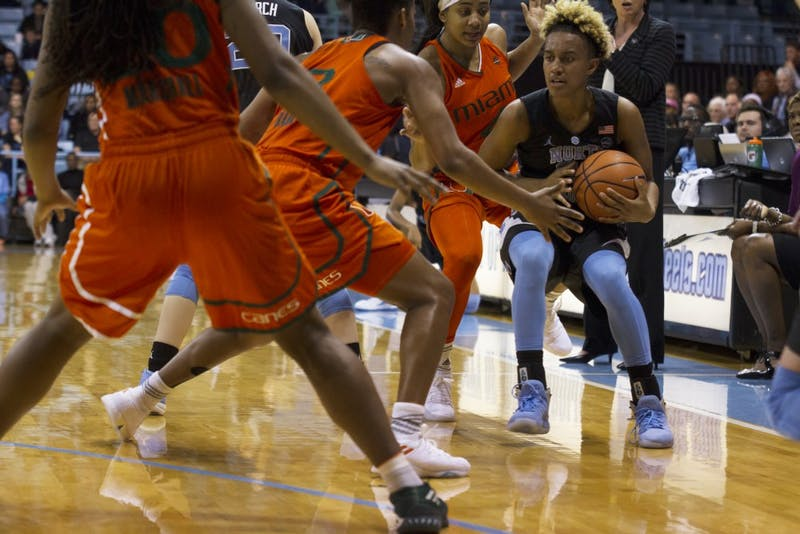 Guard Paris Kea (22) is trapped by two Miami defenders during a Feb. 4 game in Carmichael Arena.