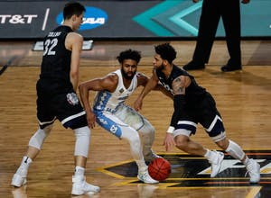 North Carolina guard Joel Berry II (2) goes between Zach Collins (32) and Josh Perkins (13) while defending during the 2017 NCAA Tournament final against Gonzaga in Phoenix.