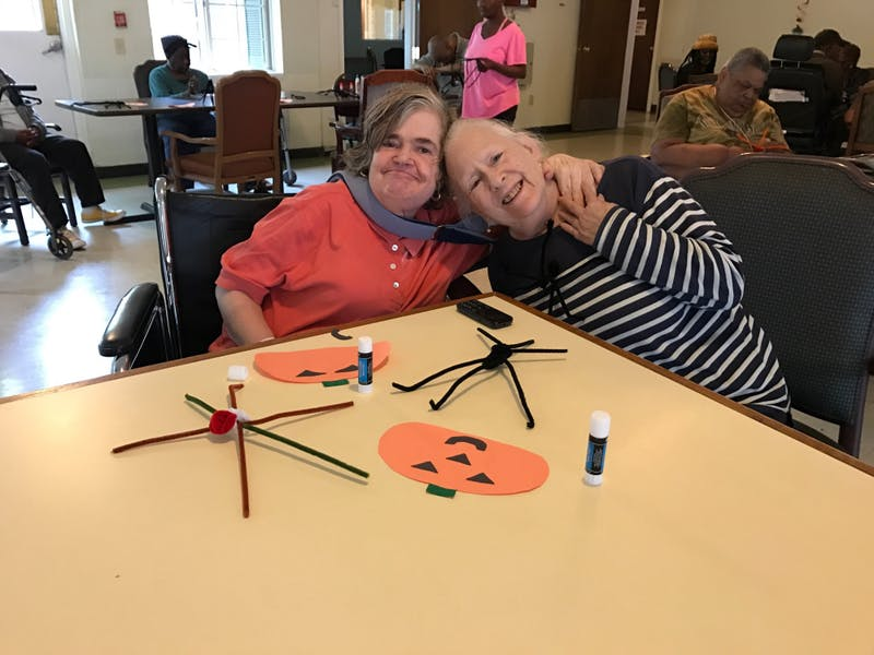 Two residents of Green Crescent Nursing Home make crafts together.