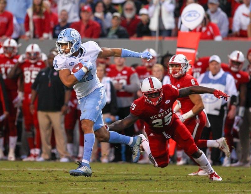 North Carolina safety Myles Wolfolk (11) returns an interception against N.C. State on Nov. 25 in Raleigh.