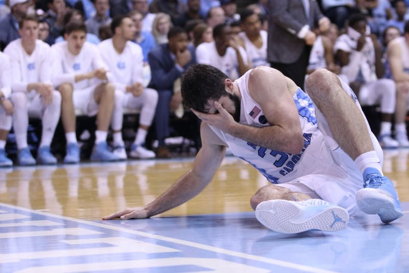 Luke Maye (32) covers his face after getting accidentally elbowed by Kenny Williams in the first half of a Jan. 16 game against Clemson in the Smith Center.