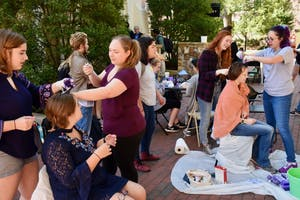 Carolina Feminist Coalition, Carolina Advocates for Gender Equality, UNC Feminist Students United, and UNC Siren come together for Paint It Purple to raise awareness for Relationship Violence Awareness month at the Campus Y.