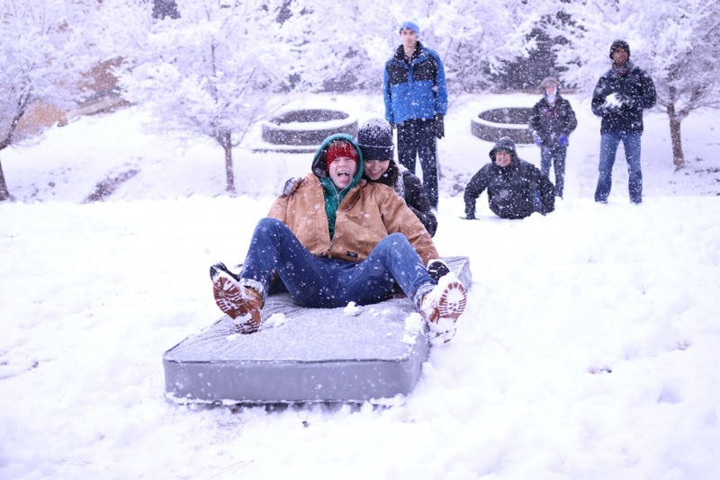First-years Grantito Everist (left) and Cat Chang (right) use a mattress to sled down the hill at the Dean Smith Center during Wednesday's snowstorm.