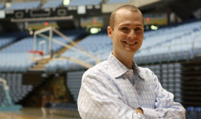 Jones Angell stands in the Smith Center. Angell, formerly a color commentator, replaced Woody Durham as the play-by-play announcer for North Carolina football and basketball in 2011.