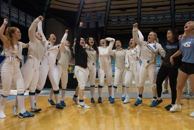 The North Carolina women's fencing team celebrates its 2018 ACC team title, the first in school history, on Feb. 24 in Carmichael Arena.
