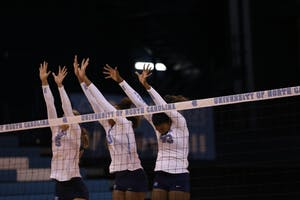 Taylor Fricano (left), Sydnye Fields (middle) and Taylor Leath (right) go up for a block in last week's scrimmage.