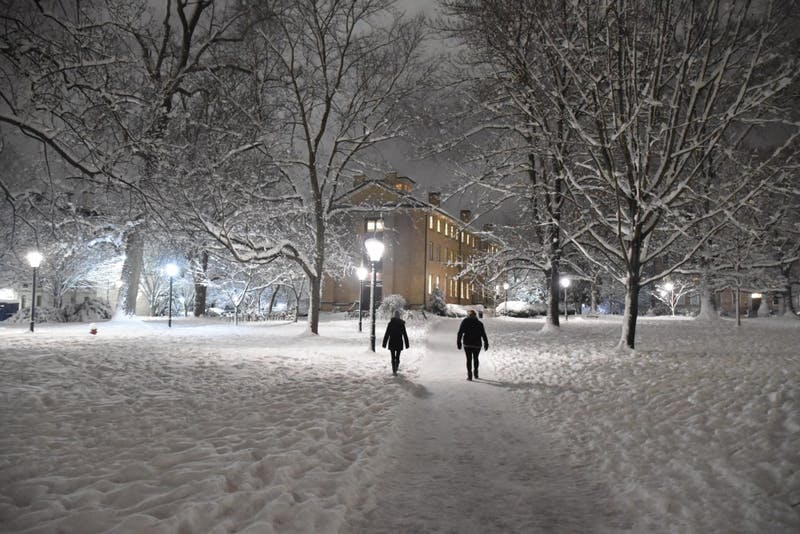 People walk through snowy North Campus on Wednesday night.