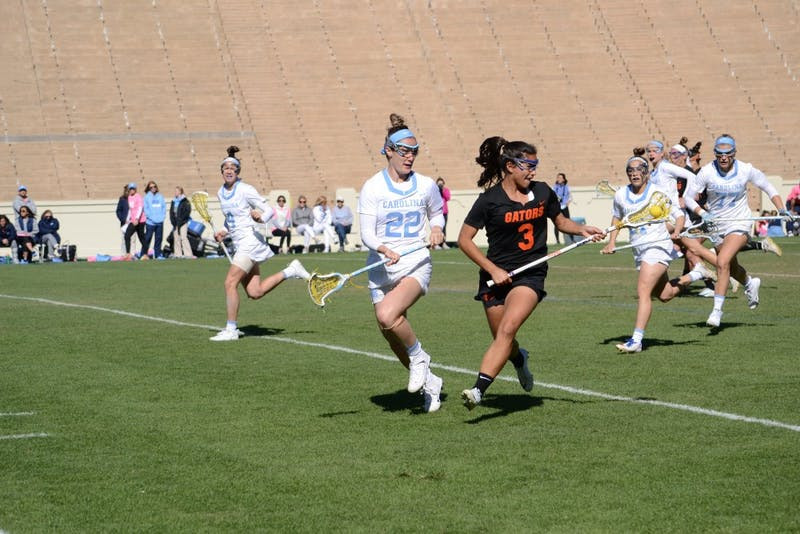 Midfielder Maggie Bill (22) plays defense against Florida during the women's lacrosse game on Saturday in Kenan Stadium.