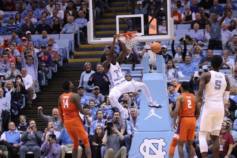 Theo Pinson (1) hangs on the rim after a dunk against Clemson on Jan. 16 in the Smith Center.
