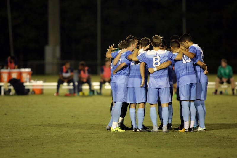 The men's soccer team huddle during a game against George Washington on Sep. 19 at WakeMed Soccer Park in Cary.