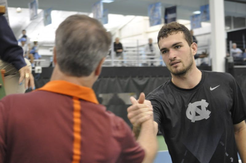 Sophomore William Blumberg shakes hands with Virginia Tech coaches on March 2 in the Cone-Kenfield Tennis Center.