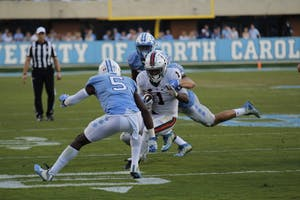 North Carolina cornerback Patrice Rene tackles Virginia running back Jordan Ellis on Saturday.