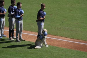 Remington joins the North Carolina baseball team on the field for the national anthem before Sunday's Fall World Series intrasquad scrimmage.