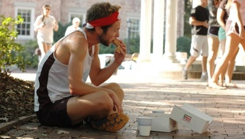 The second annual Doughnut Dash in 2012. Runners competed with a 4 mile race and eating 12 donuts. Then-sophomore Connor Belson, the first place winner, eats donuts in between running. Photo by Jason Wolonick.