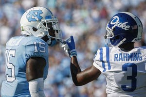North Carolina safety Donnie Miles (15) and Duke wide receiver T.J. Rahming (3) jaw during Saturday's game.