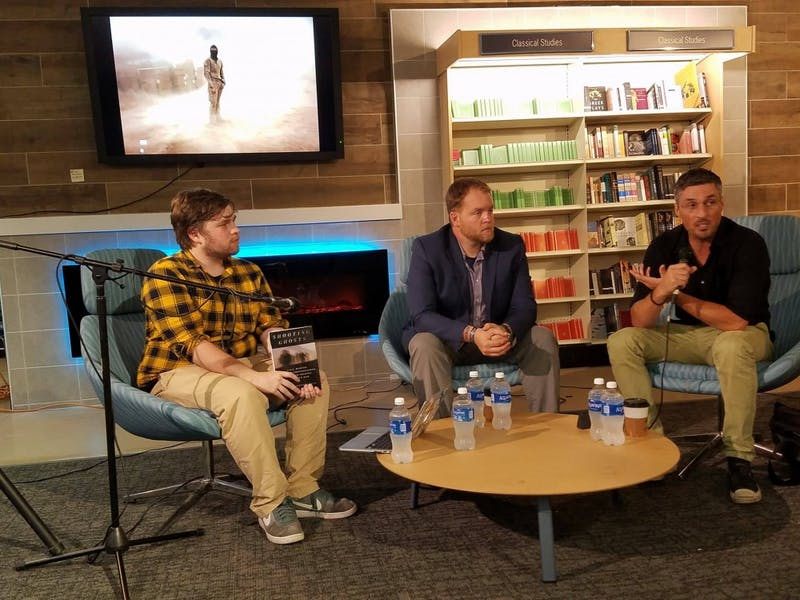 """Tyler Fleming, editor-in-chief of The Daily Tar Heel, moderates a panel with Thomas Brennan and Finbarr O'Reilly, authors of """"Shooting Ghosts."""""""