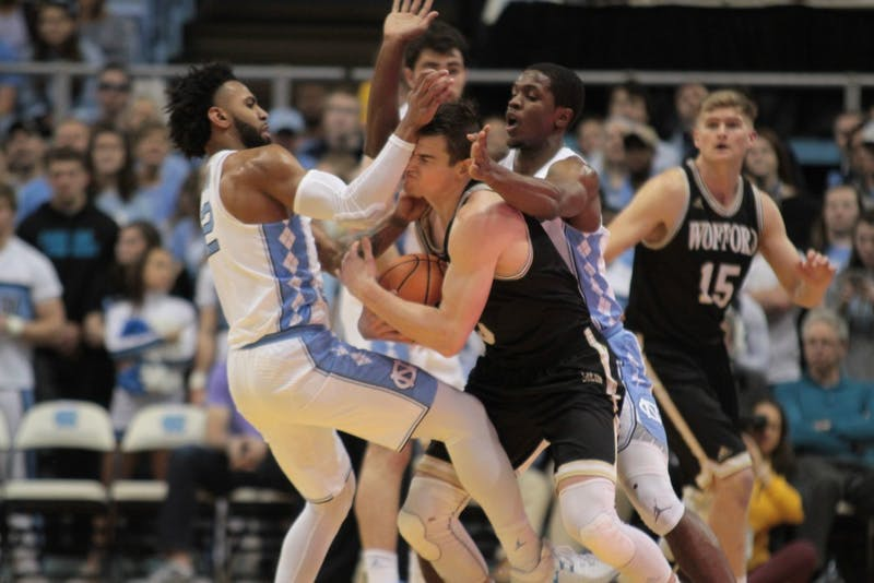 North Carolina guards Joel Berry II (2) and Kenny Williams (24) swarm Wofford guard Fletcher Magee (3) during a Dec. 20 game in the Smith Center.