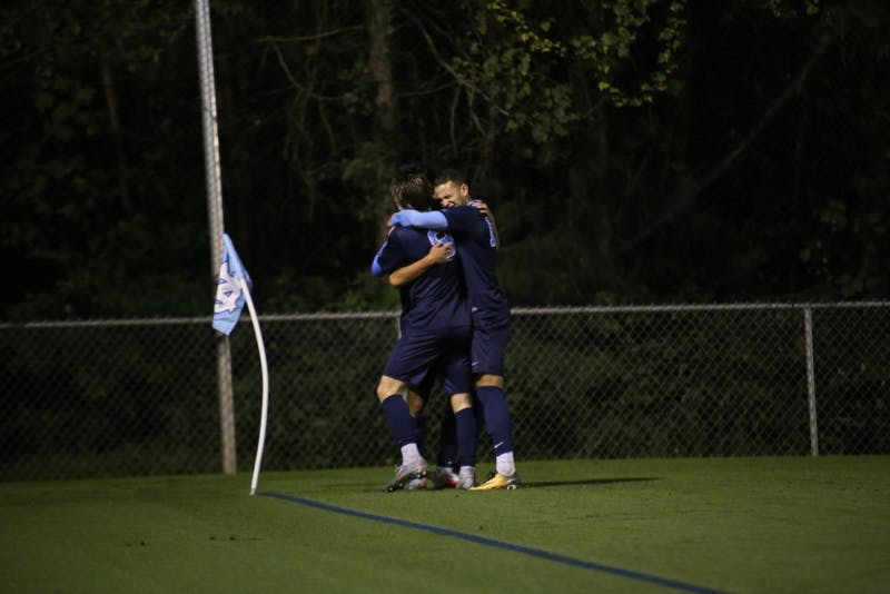 Jack Skahan and Zach Wright embrace Lucas del Rosario after he scores the game winning goal to beat Old Dominion University in double overtime.