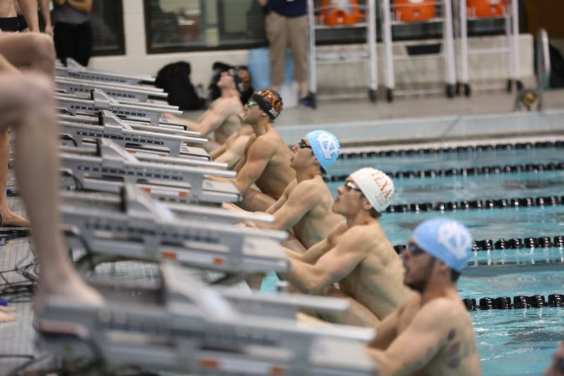 Swimmer Alvin Jiang (center) prepares to start his race against Texas on Saturday in Koury Natatorium.