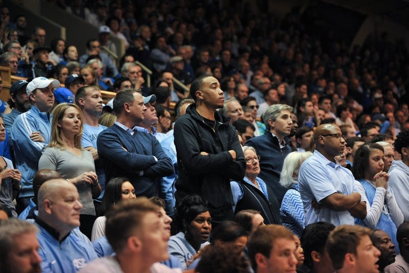 Former UNC men's basketball player Brice Johnson watches from behind the UNC bench.