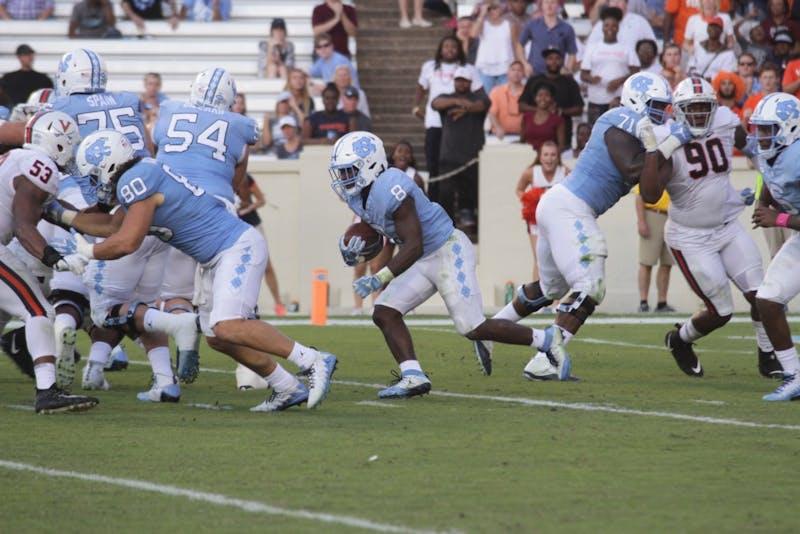 Running back Michael Carter (8) carries the ball against Virginia on Oct. 14 in Kenan Memorial Stadium.