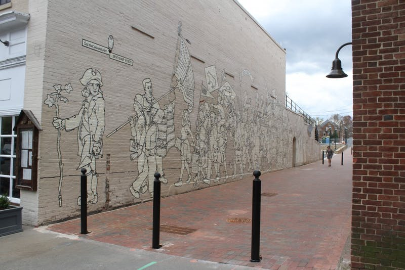 "Porthole Alley contains the ""Parade of Humanity"" mural, painted in 1997 by Chapel Hill native Michael Brown."